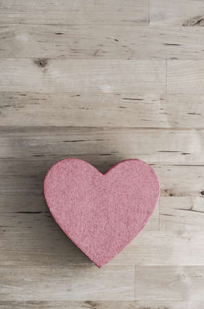 overhead shot: Overhead shot of a pink, heart shaped box in lower half of frame on an  old  light wood planked table.