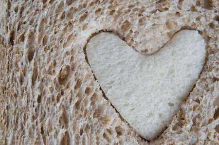 inserted: Close up of brown bread texture, with a heart shaped piece of white bread inserted.