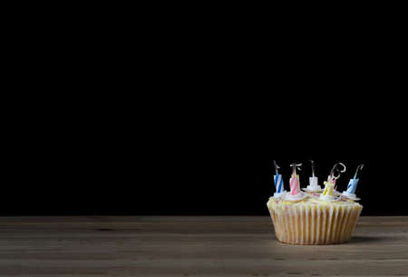 burned out: A birthday cupcake in a  plain paper case with seven striped candles that have burned down and been blown out.  Placed  on a wooden table with black background.