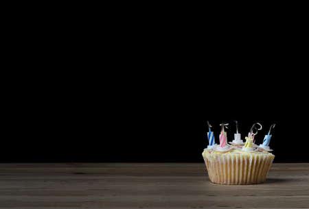 quemado: Una magdalena del cumpleaños en una caja de papel normal con siete velas rayadas que se han quemado abajo y sido sacado. Colocado sobre una mesa de madera con fondo negro.