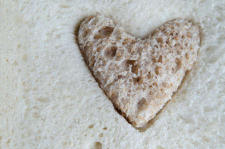 inserted: White bread with a brown heart-shaped piece of wholemeal bread inserted. Stock Photo