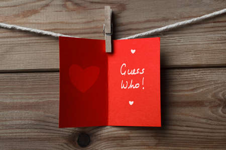 guess: An opened, red Valentines Day card pegged on to string against wood plank background with the words Guess Who written inside.