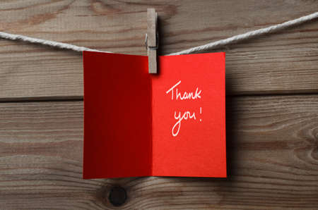 thankfulness: A red greetings card, pegged on to string against wood plank background.  Opened to display the words Thank You.