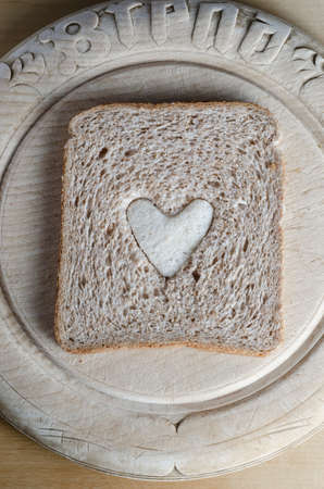 centred: Overhead shot of a slice of brown bread with white bread heart in centre, on a round vintage bread board.