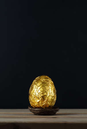 crinkled: Easter concept.  A chocolate egg, wrapped in crinkled metallic gold foil. Stock Photo