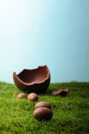 broken hill: Easter scene with small milk chocolate eggs forming a path up a grassy hill , leading to a larger egg that is broken open.  Blue sky behind and above provides  copy space.  The grass is artificial.