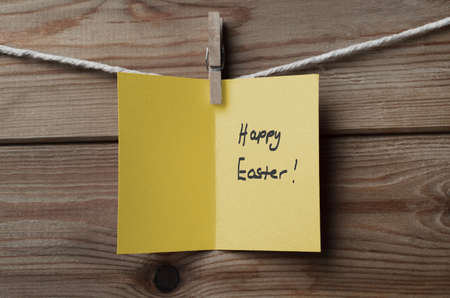 easter message: An opened, yellow greeting card, with Happy Easter message written inside, pegged to string against wood plank background