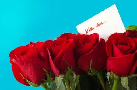 ramo de flores: Un ramo de rosas rojas contra el cielo azul de fondo. Aparece un mensaje de la tarjeta blanca muestra 'con amor' con letra roja.