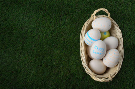 fake smile: Overhead shot of a pale wicker basket filled with hand painted Easter craft eggs and set down on artificial green grass.  Copy space to the left.