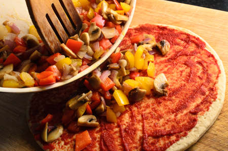 pizza base: Pizza preparation scene.  Mixed, fried vegetables being tipped on to pizza from pan with wooden spatula.