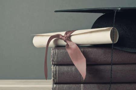 Gros plan d'une taloche et graduation défilement en haut d'une pile de vieux livres, usés, placé sur une table en bois clair avec un fond gris. Faded, lavé les couleurs pour l'aspect vintage ou rétro. Banque d'images