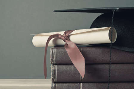 Close up of a mortarboard and graduation scroll on top of a pile of old, worn books, placed on a light wood table with a grey background.  Faded, washed out colours for vintage or retro appearance.