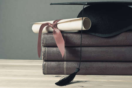 Graduation mortarboard and scroll tied with red ribbon on top of a stack of old, worn books on a light wood table.  Grey background.  Faded, washed out colours for retro or vintage appearance. Stock Photo