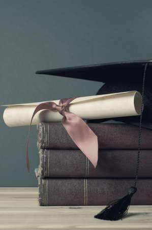 A mortarboard and parchment diploma scroll tied with ribbon, on top of a pile of old books on a wooden table.  Retro or vintage appearance with undersaturated, washed out, faded colours.