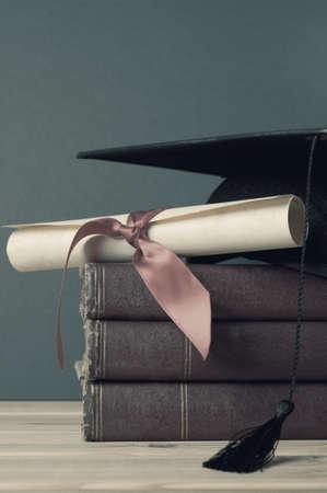 mortarboard 및 양피지 졸업장 스크롤 리본, 나무 테이블에 오래 된 책 더미 꼭대기에 묶여. 불포화, 씻겨 나갔다 색이 퇴색 한 복고풍 또는 빈티지 모양.