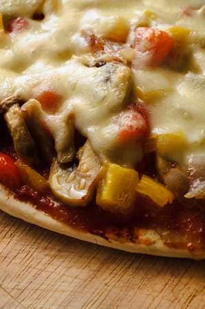 red cooked: Close up (macro) of a cooked vegetarian pizza, with red and yellow peppers, onions, mushrooms and mozzarella cheese, on scratched wooden chopping board.