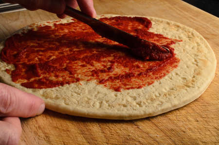 pizza base: Male hand spreading tomato base over pizza on worn, scratched wooden chopping board.  Dark lighting.
