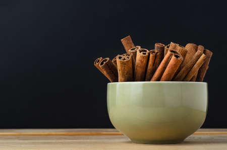grouped: Cinnamon sticks, grouped in a ceramic green bowl on wood planked table, with black chalkboard background providing copy space. Stock Photo