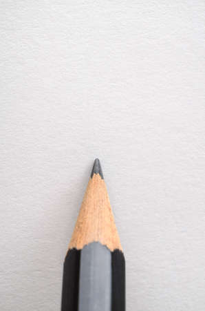 poised: A graphite pencil, poised as if about to write or draw on blank white paper. Stock Photo