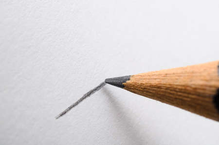 clarifying: Angled close up (macro) of a graphite pencil drawing a line on textured white paper. Stock Photo