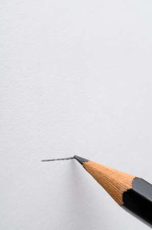 clarifying: A graphite pencil drawing a line across a blank white page.  Copy space above.