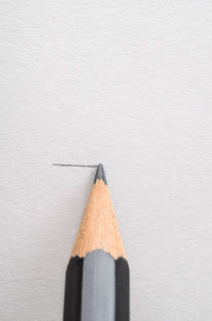 clarifying: A graphite pencil, drawing a horizontal line on white paper.  Copy space above.