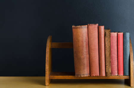 tatty: A row of old used books with blank spines, upright on a desktop shelf with black chalkboard background. Stock Photo
