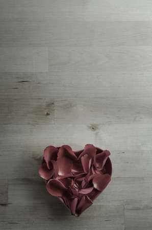 saturation: Overhead shot of plum toned rose petals filling a heart shaped bowl on an old wood plank surface background.  Low saturation for a faded retro or vintage effect. Stock Photo