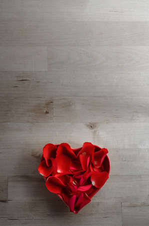 portrait orientation: Overhead shot of red rose petals filling a heart shaped bowl on an old wood plank surface background.  Low saturation for a faded retro or vintage effect. Copy space above.