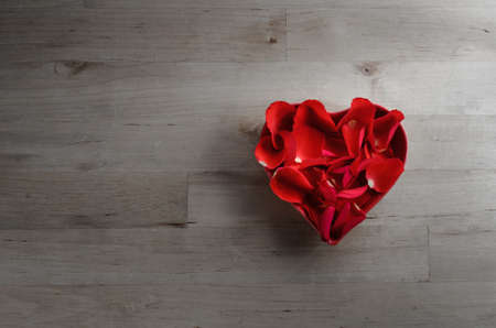 saturation: Overhead shot of red rose petals filling a heart shaped bowl on an old wood plank surface background.  Low saturation for a faded retro or vintage effect.