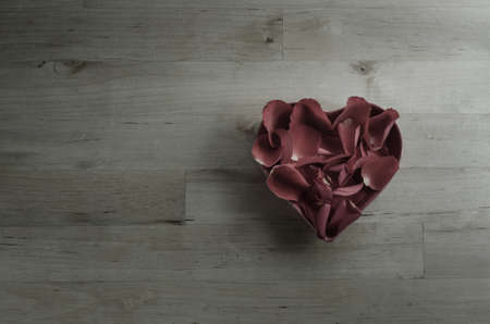 faded: Rose petals filling a heart shaped bowl, in old, faded dark plum hues.  Shot overhead on a wood planked surface.  Faded with low saturation for a moody retro or vintage effect. Stock Photo