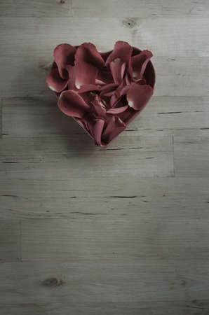 saturation: Overhead shot of rose petals filling a heart shaped bowl on an old wood plank surface background.  Plum tones and ow saturation for a faded retro or vintage effect.