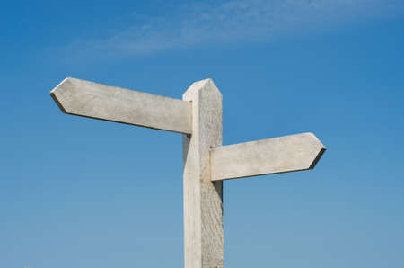 Old wooden signpost with two blank boards pointing  in different directions, weathered to white against bright blue sky with light fluffy clouds.