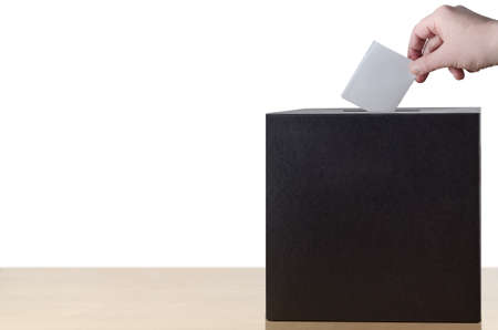 chit: Hand placing folded voting slip into slot in ballot box on light wood table.  Isolated on white background.