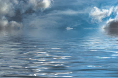 portent: Dreamy, fantasy style seascape with blue sky and threatening grey clouds.  The sky iis real with water added artificially. Stock Photo
