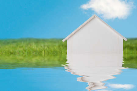 Conceptual photograph of a white wooden house in bright green grassy landscape with blue sky, appearing to sink into a flood of water.  Water has been added artificially.