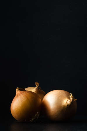 grouped: Still life of three whole, unpeeled onions, grouped on black slate with black chalkboard background providing copy space above.
