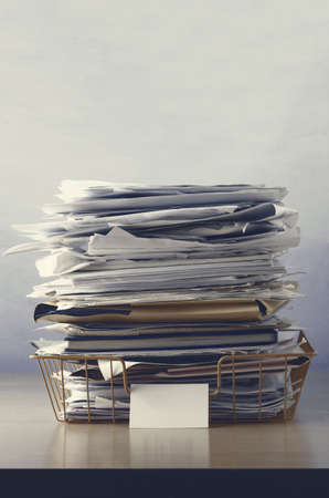drab: A wire office tray with blank label, piled up with papers and folders, undersaturated in drab hues for dreary, dystopian feel. Stock Photo