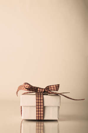 adjusted: A white Christmas or celebration gift box tied with gingham ribbon on reflective surface.  Hues adjusted for retro or vintage effect.  Copy space above. Stock Photo