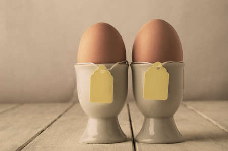 adjusted: A pair of brown eggs in eggcups with price tag style labels on string.  Old white wooden planked table.  Hues adjusted for retro or vintage appearance.