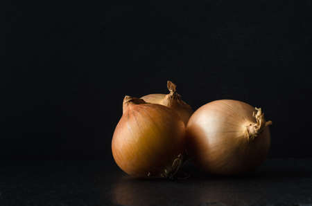 onion peel: Three onions grouped in still life composition on slate surface with black chalkboard background and copy space.