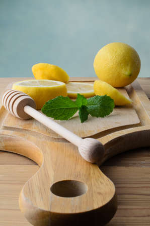 drizzler: Whole and sliced lemons with mint leaves and honey drizzler on  wooden chopping board with pine kitchen table below. Stock Photo