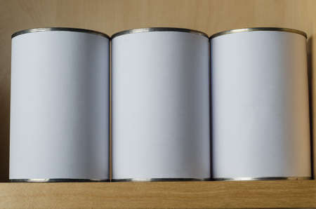 long lasting: Three tin cans in a row, on a shelf above eye level, with blank white labels for copy space.