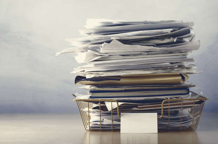 untidy text: An old wireframe filing tray, piled high with documents and folders, on a light wood veneer desk.  Drab hues for dreary, dystopian feel. Stock Photo