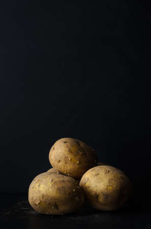 unpeeled: A still life group of fresh, whole, unpeeled potatoes with scattering of soil on black slate with black chalkboard background providing copy space above.