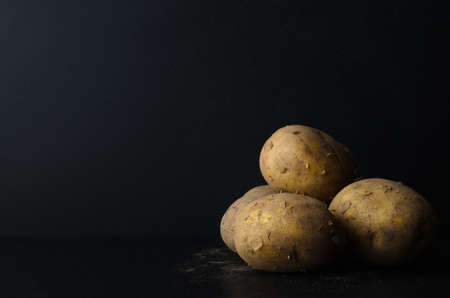 unpeeled: A group of freshly harvested, whole, unpeeled potatoes on black slate with a dusting of soil.  Black chalkboard background provides copy space.