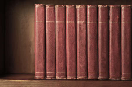 spines: A row of old, battered, matching encyclopaedias (circa 1950s) lined up on a shelf, with titles removed to leave blank spines.  Red leather effect with gold striped trims.  Vintage effects applied. Stock Photo