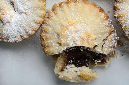 expose: Close up of one of three Christmas mince pies, broken open to expose filling, with crumbling pastry.