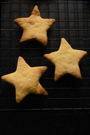 portrait orientation: Overhead shot of three star shaped, home baked Christmas biscuits (cookies) on a black wire cooling rack. Stock Photo
