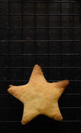 imperfect: Overhead shot of a single, imperfect star shaped Christmas biscuit, freshly baked and placed on a black wire cooling rack.